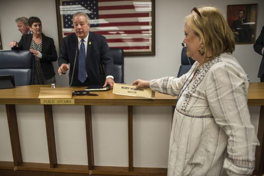 Outgoing executive director Sally Cody switches out the name plates during a village hall meeting at the Village of Forest Park. | Alexa Rogals/Staff Photographer