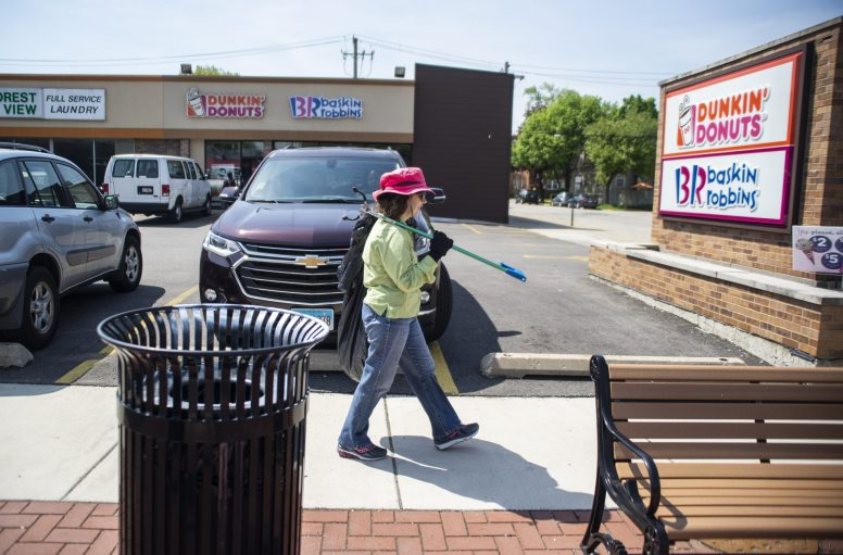 """Ellen Waterman, of Forest Park, looks for trash to pick up on during a """"plalking"""", also known as picking up litter while walking along Madison Street in Forest Park. 
