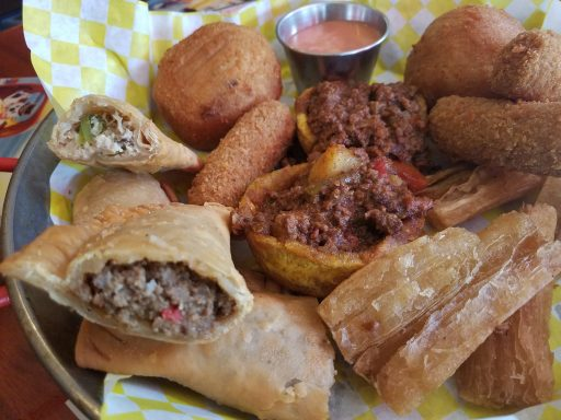 The tapa combo features 2 papas rellenas, 2 beef empanadas, 3 ham and cheese croquettes, 2 beef tostones, and yuca frita.