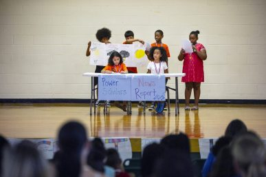 Rising fifth graders perform a mock news report during the Power Scholars Academy closing ceremony at Forest Park Middle School in Forest Park. | Alexa Rogals/Staff Photographer