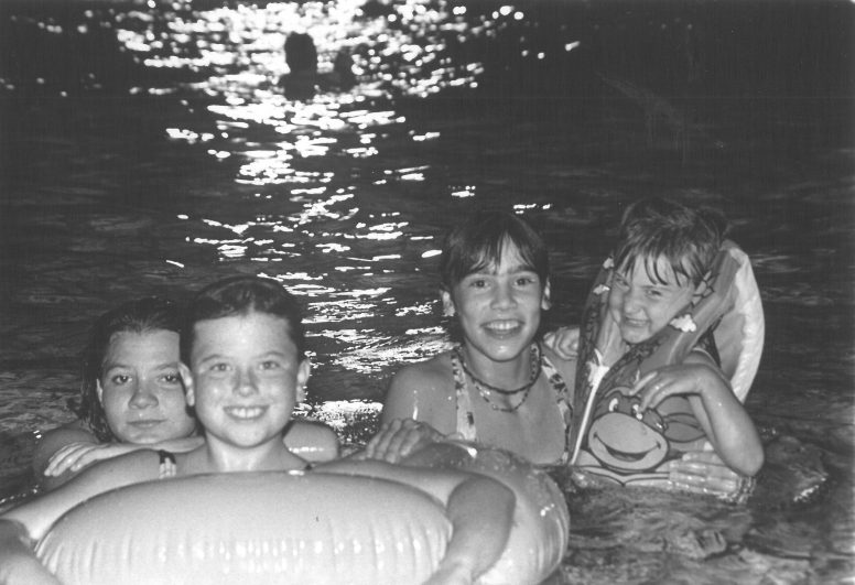 Forest Park Pool Party August 7, 1993, These four girls take time to smile for the camera as they enjoy the evening swimming and floating the night away.