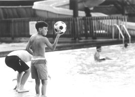 Matt Montes adds a soccer ball to the pool at the Soccer League Pool Party in 1994.