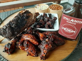 """The """"small batch"""" from Small Batch Barbecue feeds 3-5 people shown here with two specialty menu items (beef rib and pork belly burnt ends) as well as smoked wings, beans and coleslaw."""