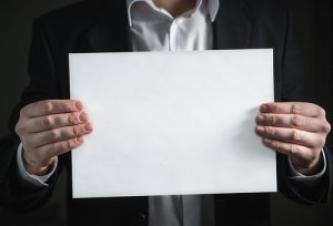 man in a suit holding a white bond paper