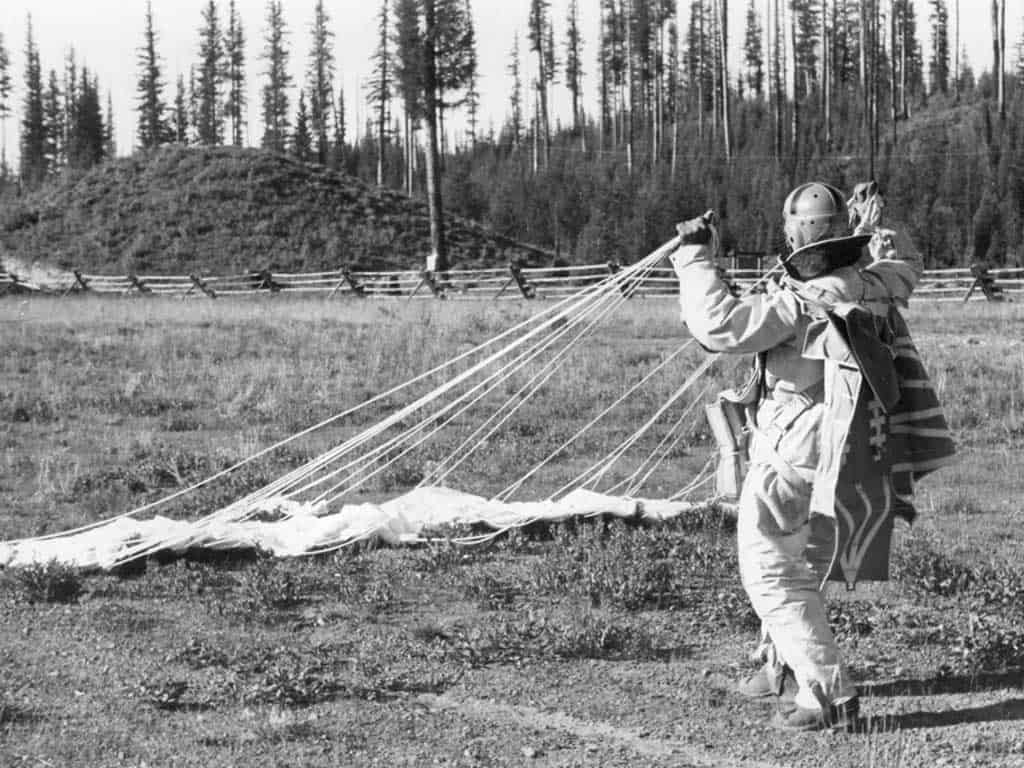 A smokejumper gathers his chute after landing in Seeley Lake, Mont., c. 1940. The smokejumper program started in 1939 as a way to reduce the time it took for crews to reach wildland fires.