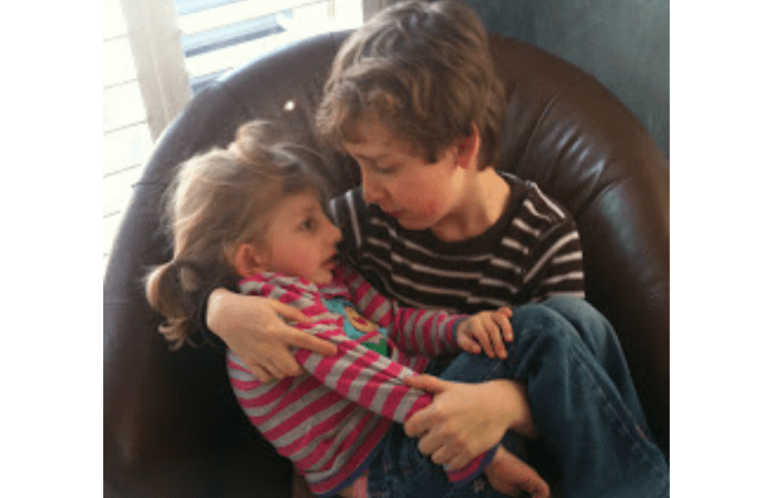 A young boy and his little sister cuddle in a chair together. She's curled up his lap and he's looking at her sweetlly.