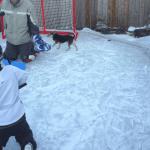 boy on his knees on backyard skating rink shooting a puck