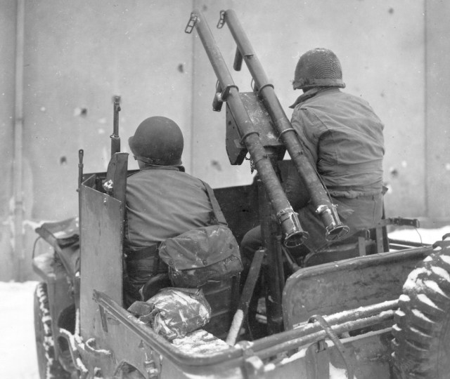 US troops in an armored Jeep with a pair of bazookas mounted on the gun pintle
