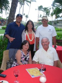Enjoying the evening of delicious crisp won ton, barbecue slicers, mini manapua, spinach quiche, vegetable platters with fruit, cheese, crackers and yummy chocolate covered cheesecake pops are: standing l-r Outer island visitor Kamika Casco, the Athletic Director from Maui Preparatory Academy in West Maui, Directory of Sales at KBR, Janice Ishihara, & Patrick Porter. Seated: residents Linda and John Low.