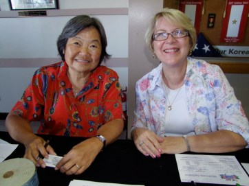 Volunteer greeters Glenda Nogami Streufert (l) and Joye Irwin