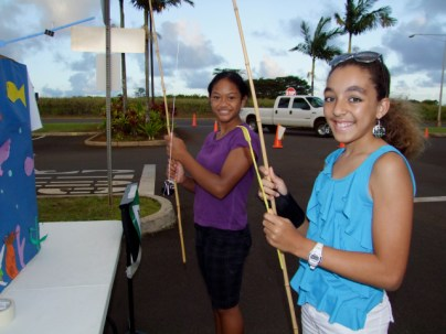 Leona Sime, (l), 7th grader; and Renee Anderson-Navarro (r), 6th grader, work the fishpond.