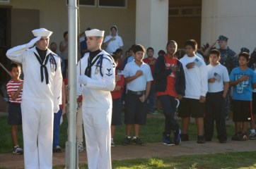 Master at Arms 2nd Class Clinton Reese and Master at Arms 3rd Class Randy Christensen conduct morning colors at St. Theresa's Catholic School during a Veterans Day celebration. Ten sailors assigned to the Pacific Missile Range Facility participated.