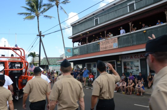 Sailors assigned to the Pacific Missile Range Facility wave to spectators during the annual Kaua`i Veterans Day Parade. Over 20 sailors participated in the parade.