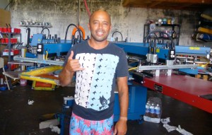 Kyle Maligro flashes a shaka while standing in front of his screen printing press at Doxa Print in Kalaheo. Photo by Viviane Gilbert Stein