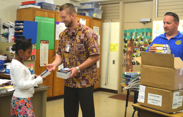 Rotary Club of West Kauai President Kevin Allison helps pass out dictionaries to third-grade students at Eleele Elementary School, Feb. 27, as club secretary Jay Gautney readies another batch of books to be handed out. More than 100 third-grade students at four schools received student dictionaries as part of the club's annual community program. (Photo by Stefan Alford)