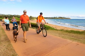 Dr. Randy Blake is seen walking Caesar, and Tommy Noyes is seen riding a bicycle on the Ke Ala Hele Makalae.