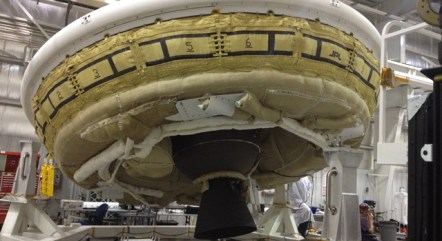 A saucer-shaped test vehicle holding equipment for landing large payloads on Mars is shown in the Missile Assembly Building at the US Navy's Pacific Missile Range Facility on Kaua'i.