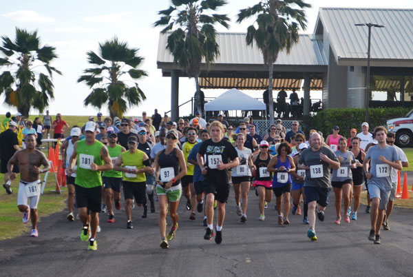 "More than 100 runners take off at the start of the Pacific Missile Range Facility's 5K Sunset Run, July 19. A field of 107 total participants from all over Kauai ran the course from Shenanigans restaurant winding to the south gate and back as the event was open to the general public.  Jackie Reding of Kapa'a came in first place overall with a time of 21:09, followed immediately by second-place finisher and first in the men's division Brian Reynolds, at 21:10. Robert Russell placed third with a 21:48 finish. ""It was great to see more than 100 runners come out, including entire military families and our local Kauai neighbors,"" said Morale, Welfare and Recreation Director William Bray. ""This was the largest run in quite a while on PMRF and the Fit Crew is already working on the next major event planned around Halloween."" (Photo by Stefan Alford)"