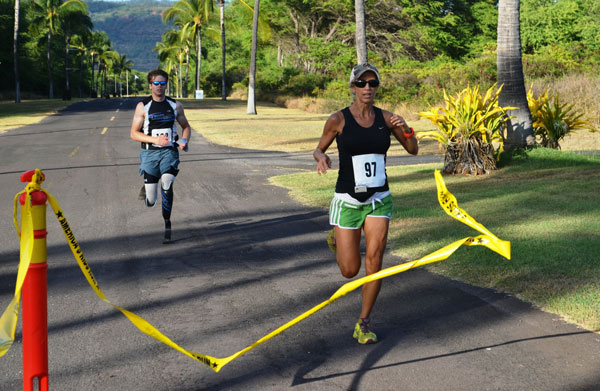 "Jackie Reding just edges Brian Reynolds at the finish line of the Pacific Missile Range Facility's 5K Sunset Run, July 19. A field of 107 total participants from all over Kauai ran the course from Shenanigans restaurant winding to the south gate and back as the event was open to the general public.  Reding from Kapa'a came in first place overall with a time of 21:09, followed by second-place finisher and first in the men's division Reynolds, at 21:10. Robert Russell placed third with a 21:48 finish. ""It was great to see more than 100 runners come out, including entire military families and our local Kauai neighbors,"" said Morale, Welfare and Recreation Director William Bray. ""This was the largest run in quite a while on PMRF and the Fit Crew is already working on the next major event planned around Halloween."" (Photo by Stefan Alford)"
