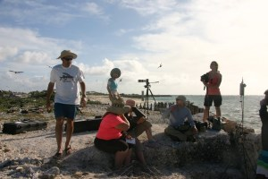 """UAS team at Shell Beach on Tern Island. NOAA UAS Project Lead Todd Jacobs (left, standing), USFWS <div class=""""fusion-title title fusion-title-size-one"""" style=""""margin-top:0px;margin-bottom:31px;""""><h1 class=""""title-heading-left""""></h1><div class=""""title-sep-container""""><div class=""""title-sep sep-double"""" style=""""border-color:#e0dede;""""></div></div></div> Michele Kuter (seated, in pink), NOAA Puma operators ENS Kerryn Schneider (looking into viewer) and LTJG Tanner Sims (seated, right), with filmmakers Andrew (standing, in background) and Robin Eitelberg (standing, with camera) on hand."""
