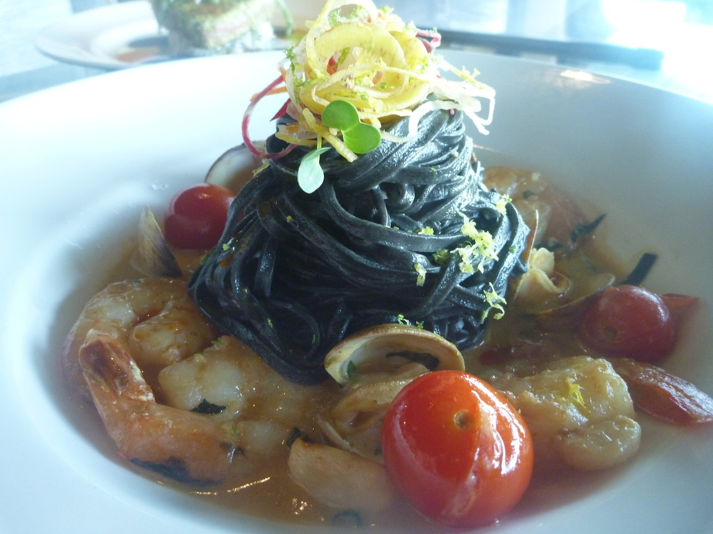 The Kaua'i Shrimp and Clams is all about seafood: It's a play on the classic Italian clam pasta but with an Asian flare. The broth is a thai-curry coconut lobster broth. The clams and the shrimp came from just down the road at Kauai's shrimp farm, and the shrimps are big and meaty. The pasta is squid ink.