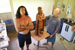North Shore artist Saim Caglayan works on King Kaumuali'i's statue while Keao NeSmith models.