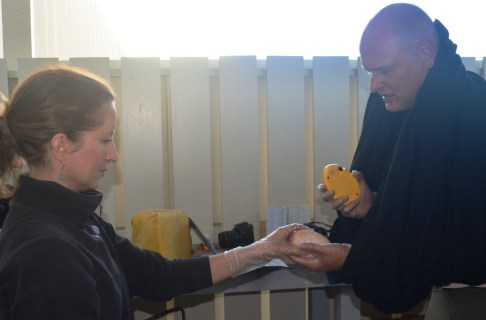 """From left, Lindsay Young and Eric VanderWerf, Pacific Rim Conservation biologists, prepare to """"candle"""" an egg at PMRF, Dec. 16 – a procedure that illuminates the shell to confirm viability. Photo by Stefan Alford"""