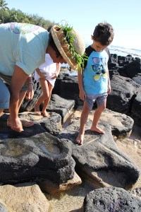 Napua Romo shows Adrien Smith lava rocks early Hawaians used to sharpen tools.
