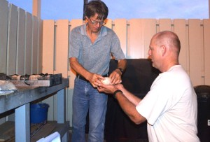 From left, Tom Savre, PMRF Natural Resources Biologist with Naval Facilities Engineering Command Hawaii, hands a Laysan albatross egg to Eric VanderWerf, Pacific Rim Conservation biologist, to ready for packaging and transport. Photo by Stefan Alford