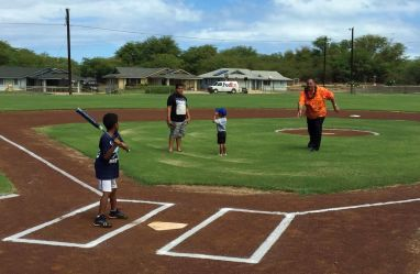 "Mayor Bernard Carvalho, Jr. throws the ""first pitch"" at the newly completed Kekaha Gardens' Kaleimanu Park. On the field with the Mayor are Makaio and Marques Hickson and Loea Pantohan."