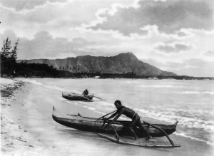 Two native Hawaiians are seen here with outrigger canoes in Waikiki circa late 1800s.