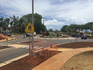The Umi and Hardy streets roundabout intersection now provides pedestrians with protected mid-crossing refuges for safer and more attractive crosswalks. Tommy Noyes demonstrates how bicyclists easily blend in with cars and trucks due to sedate speeds in the roundabout. This makes cycling in the street the preferred option and leaves the sidewalks for pedestrians. Photo by Pat Griffin.