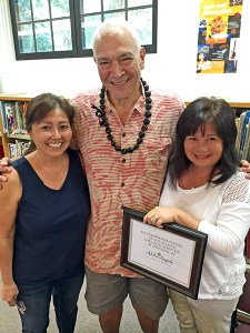 Aloha Angels Donor Paul Horner, general manager of The Club at Kukui'ula, embraces Sharlyn Kanna, left, and Sulyn Hashimoto, two of the four Kalaheo teachers whose classes he adopted, at a faculty meeting last Wednesday. Contributed photo