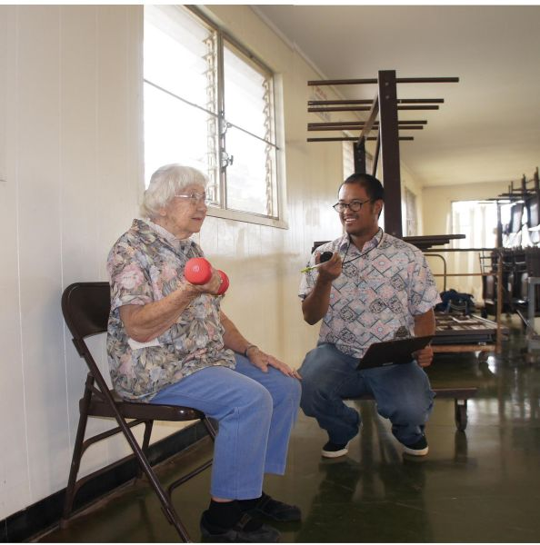 "Jacquelyn ""Jackie"" Schoening, a participant in the EnhanceFitness program, demonstrates to Program Coordinator Johnny Yago how she has learned to use a dumbbell."