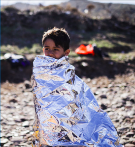 A young boy from Syria is seen here wrapped up in an emergency blanket, standing on the beach of Lesvos, Greece, after arriving with his family in an inflatable boat from Turkey earlier this year. Photo courtesy of A. Zavallis/UNHCR