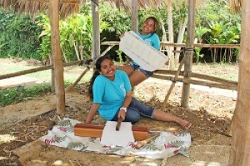 Kawaikini Public Charter School senior Jaclyn Ku'uleimomionalani Ka'ahanui, left, and sister Jaylyn Kawaiopua-Ululani Ka'ahanui, a junior at the school, are seen here holding kapa and kapa making tools at the hut built by students in the school's Hawaiian garden.