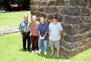 From left to right, Niles Kagayama, Setsuko Kobayashi and husband Toshio Kobayashi, and Toshihiro Otani at the smokestack that was part of the third sugar mill built in Kōloa, in 1841.