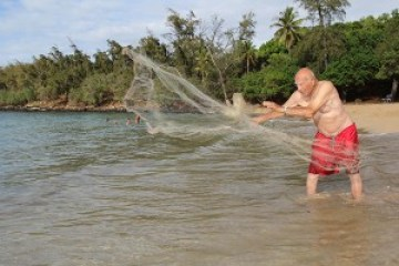 Uncle Charlie demonstrates how to throw net at Smith's Beach in Anahola.