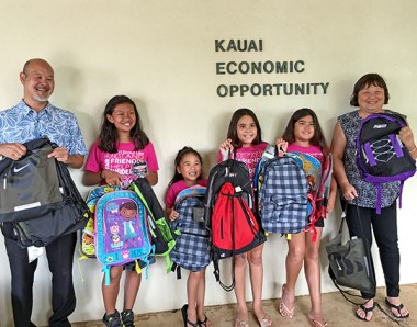 Girl Scouts of Hawaiʻi Troop 988 members (left to right) Cairee, Tianny, Danika, Kaori, and Stephanie assembled backpacks as part of the Kaua'i Economic Opportunity Homeless Program.