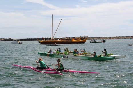 Several outrigger canoes escort the Nāmāhoe to Kalapaki Bay