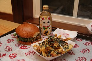 The Kenji Burger (grass-fed beef patty over white rice, topped with spicy teriyaki, ponzu aioli, caramelized onions and cheddar cheese), served with furikake fries, mochi and Lucky Cat soda.