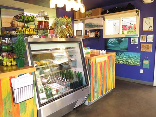 Anuenue Café's counter is crowded with fresh produce and tropical colors.