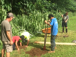 Kalo Farmer and Kawaikini Makua, Adam Asquith, leads students in the initial school garden fence build at Kawaikini.