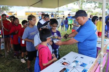 Kaua`i Board of Water Supply member, Michael Dahilig (far right) shows students the beads that will represent clouds in their journey through the water cycle; part of the Incredible Journey activity tent at Department of Water's 14th Annual Make a Splash festival on Sept. 28, 2017.