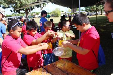 Fifth graders from King Kaumuali'i elementary work together to transport their single water source through a water-related obstacle course at the Make a Splash festival.