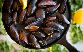A sizzling skillet of mussels, served with garlic, herbs and chili lime butter.