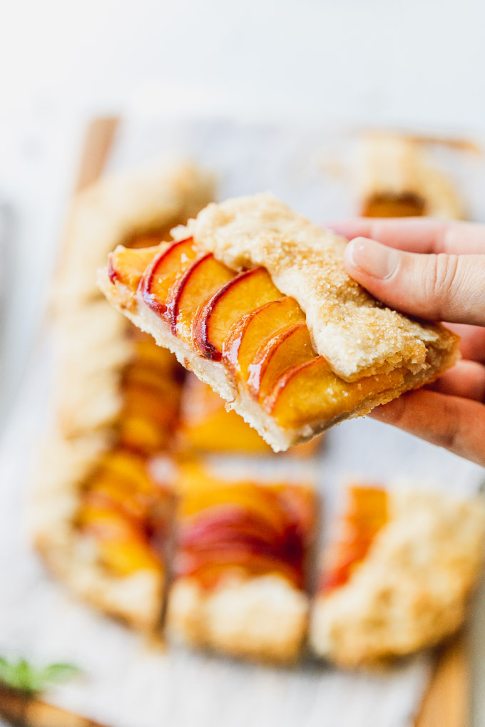 holding a slice of peach galette