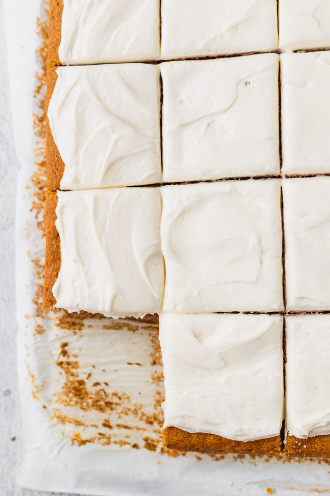 overhead of cut pumpkin bars with cream cheese frosting