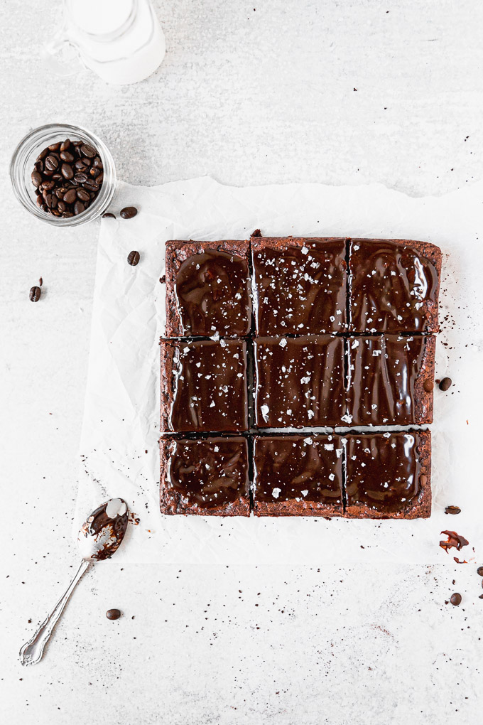 overhead brownies cut into squares with espresso beans and spoon
