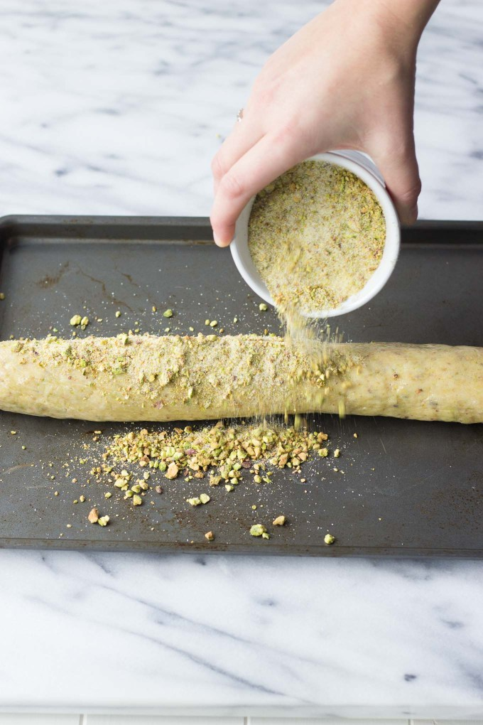 Pistachio Butter Cookies pouring pistachios on log of dough // Fork in the Kitchen